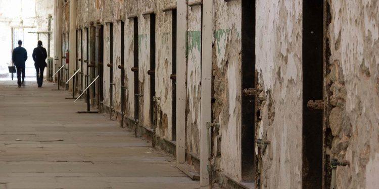 people walking along old jail cells
