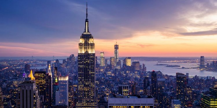brightly lit New York City skyline at dusk