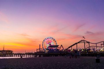 roller coasters and festival rides at Santa Monica pier at sunset