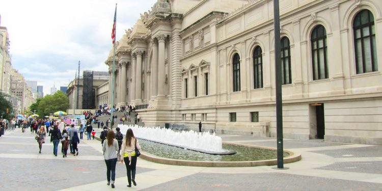 people walking in front of the Metropolitan Museum of Art in New York City