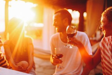 flare from sunset shines over friends laughing