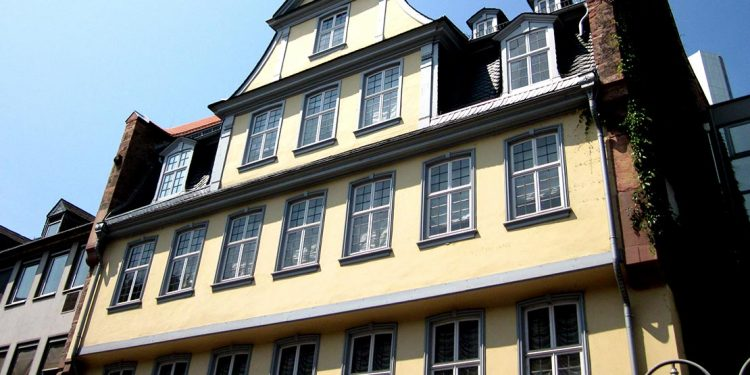 close up of yellow house with many windows