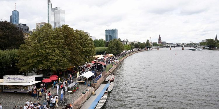 tourists bustle through shops by the river