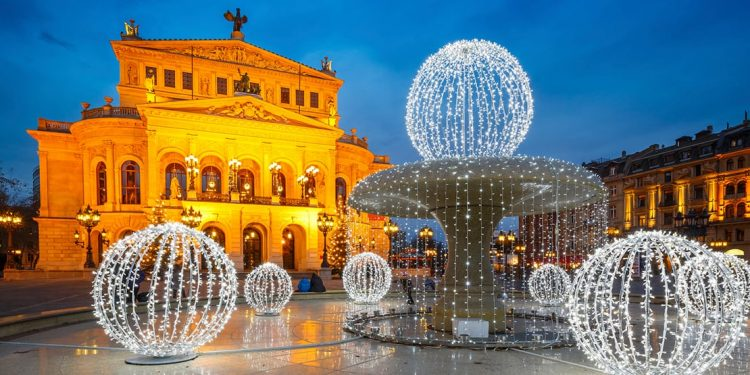 building with stunning architecture and fountain draped in christmas lights