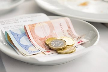 euro coins and bills folded in a white dish