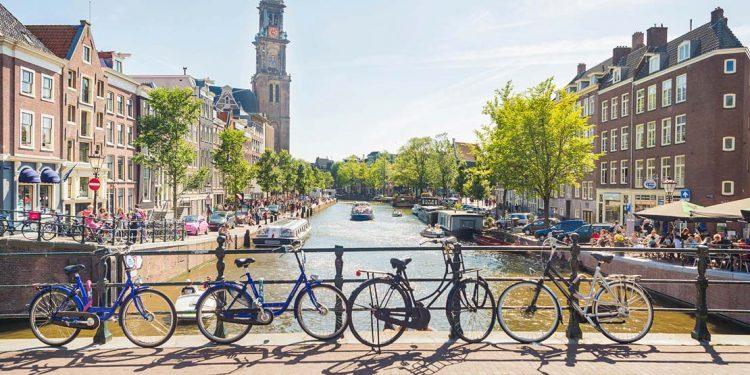 bikes line bridge overlooking channel in amsterdam, netherlands