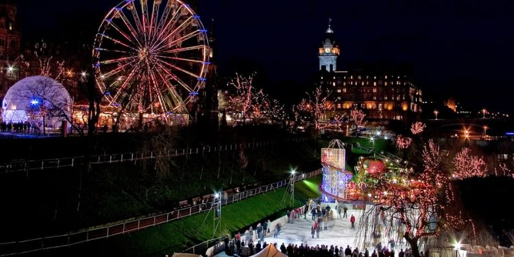 trees covered in christmas lights while patrons skate on ice rink at night in edinburgh, scotland