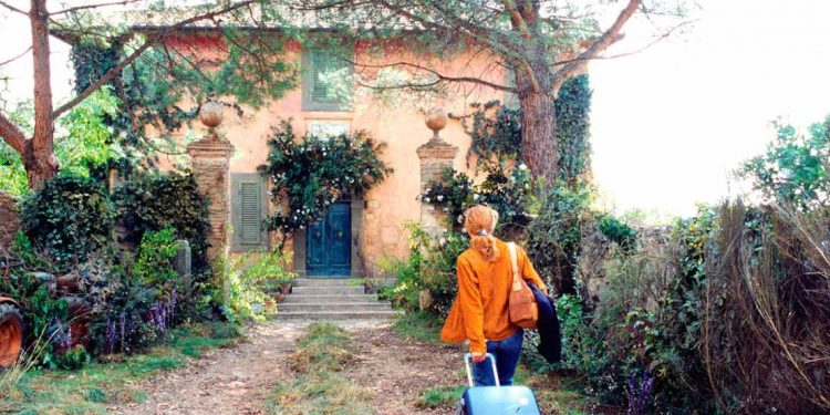 woman pulling suitcase up laneway of old home covered in vines