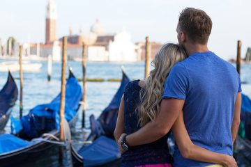 Young couple leaning into each other and looking out over moored boats