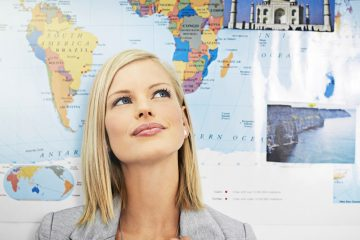 woman daydreaming in front of world map poster