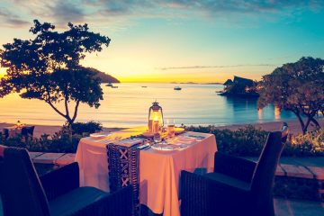 table for two overlooking ocean at sunset