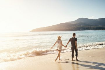 couple holding hands walking down the beach