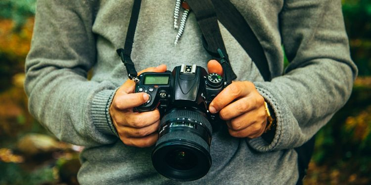 Man in a grey sweater holds a DSLR camera