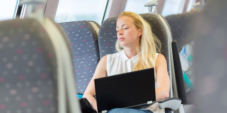 Woman with a laptop on her lap sleeps on a train