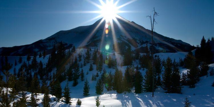 The sun sits atop a ski hill at Big Sky, Montana