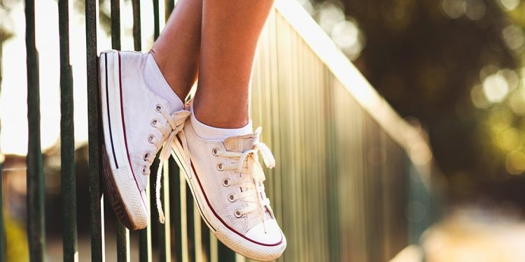 Feet wearing comfortable sneakers dangle over a green fence