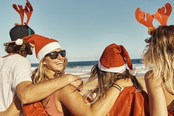 Group of smiling young people on a beach wearing Santa hats and reindeer antlers