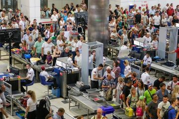 Overhead shot of hundreds of people making their way through airport security