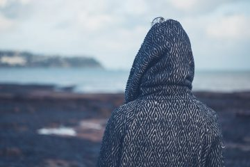 Person in a hooded sweatshirt stares looks out over a rocky beach