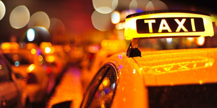 Row of taxis with their lights on at night