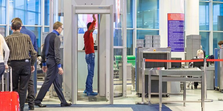 Man stands with his hands up in a scanning machine at the airport