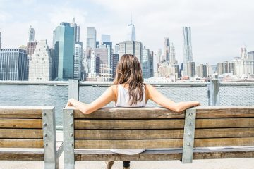Woman sits on a bench looking at the New York skyline