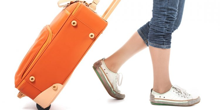 Woman in sneakers and jeans pulls an orange suitcase behind her