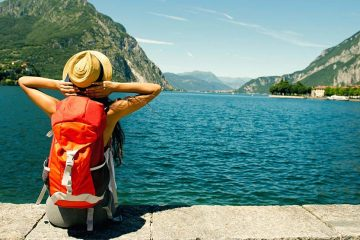 Woman wearing a backpack sits on the edge of a seawall looking out at the water and mountains in the distance
