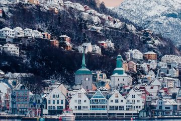 Snow covered buildings in Bergen, Norway, with a mountain in the background