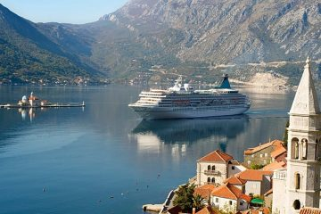 Cruise ship floats past a town with mountains in the background