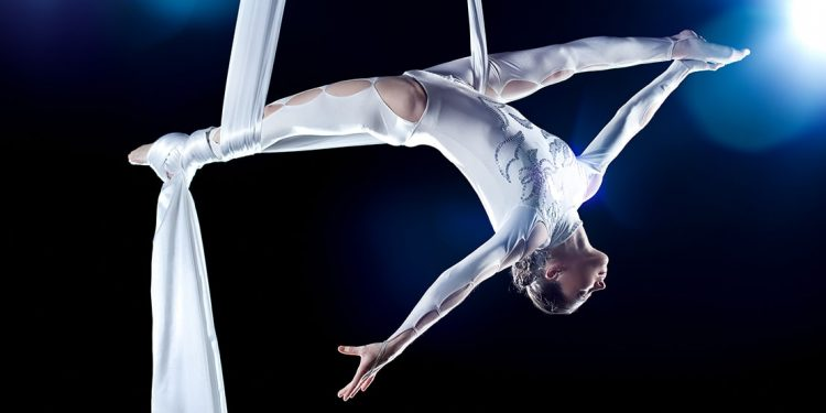 Acrobat in a white costume performs with aerial silk