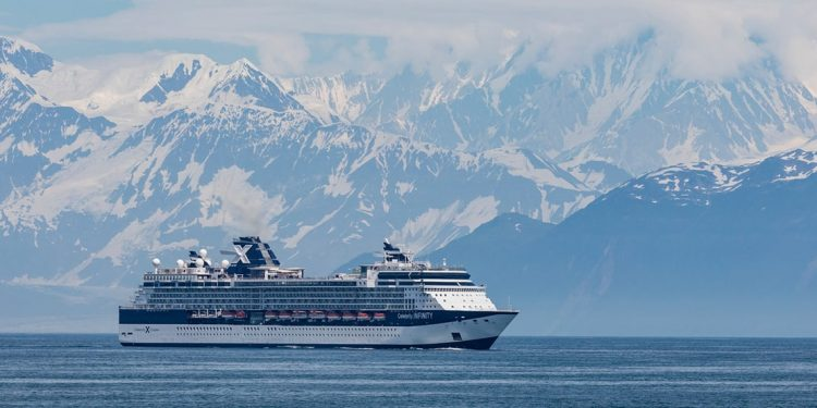 Cruise ship floats past snowy mountains