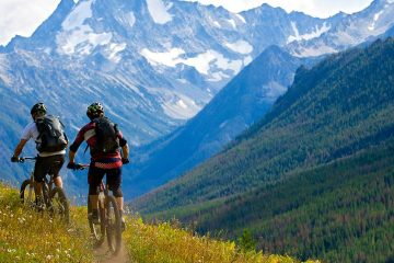 people riding bikes through the mountains