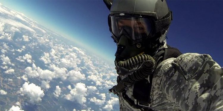 Person wearing oxygen mask falling through the sky