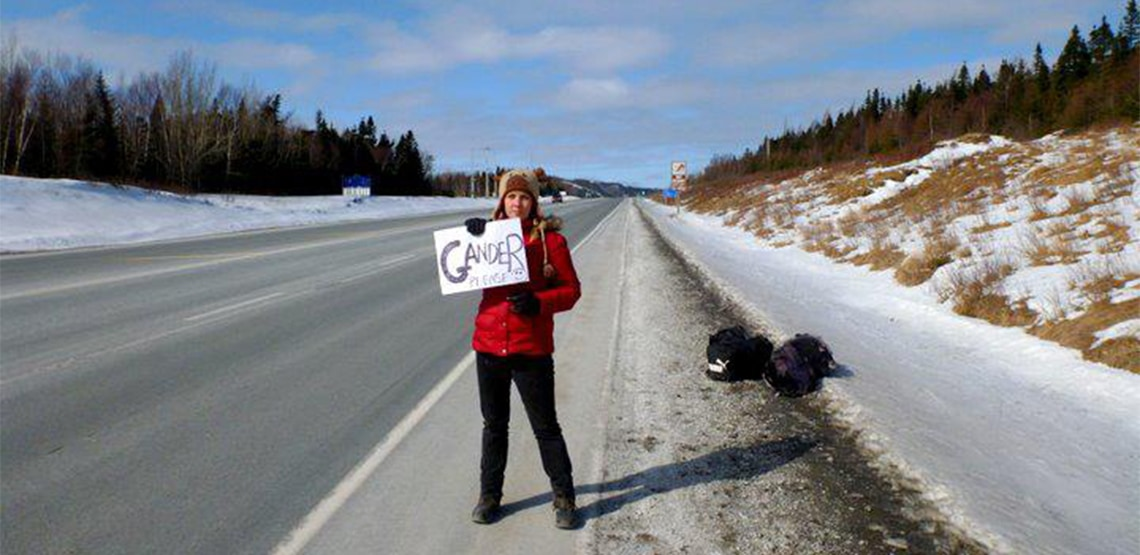 Kelly stands on the side of a road holding a sign that says 'Gander please'
