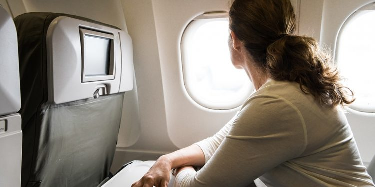 Woman sitting in a plane leans on her tray table and looks out the window