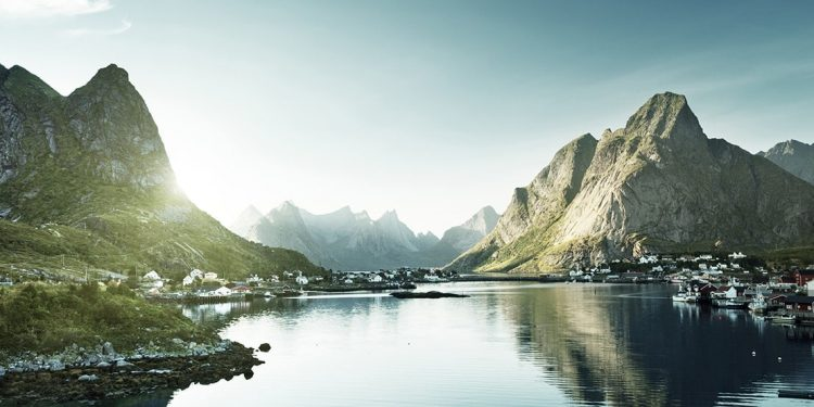 Mountains rise up on either side of a river in Norway