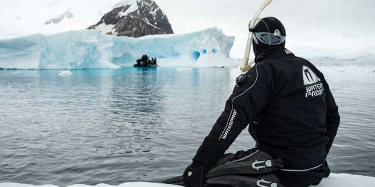 Person in wetsuit and scuba gear sits on an ice shelf with their feet in the water