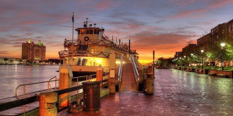 boat docked at harborfront at sunset