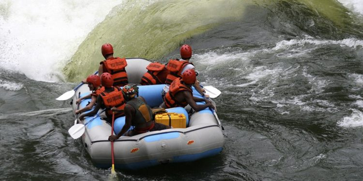 7 people in a rubber raft wearing helmets and life jackets about to go over large rapids