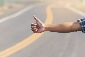 An outstretched arm giving the thumbs up on the side of a road.