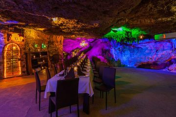 A large dining table is surrounded by colorful blue, purple and green lighting, in a cave setting