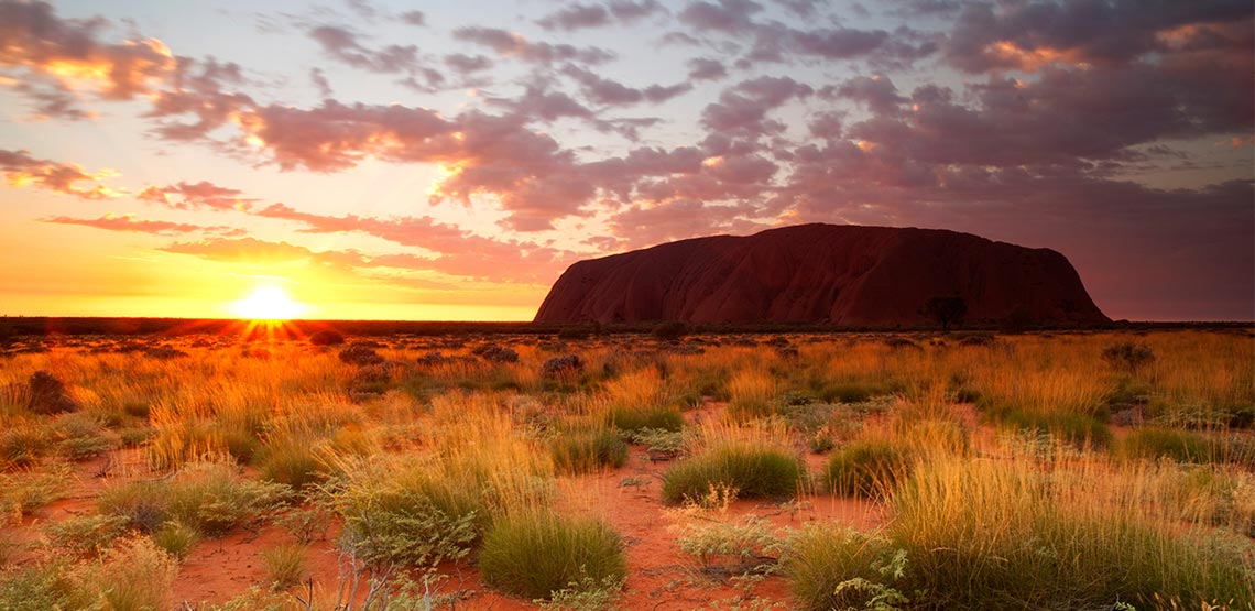 Uluru, or Ayers Rock, a sandstone monolith in Australia is on the right side of the sun setting