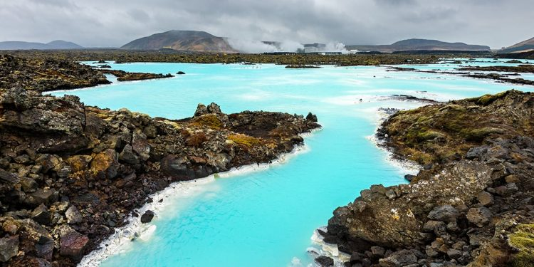 A geothermal spa with vibrant aquamarine colors is surrounded by natural rock formations