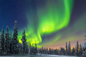 The Northern Lights show colors of green, orange, and red around snow-covered cedar trees