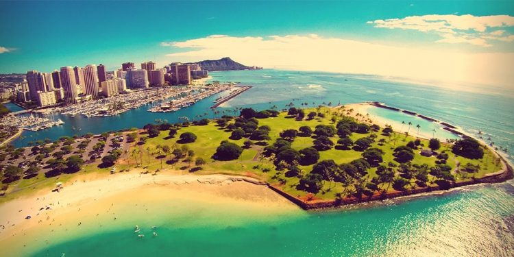 large park with walkable trails and two beaches includes a Hawaiian city is in the background with boating docks