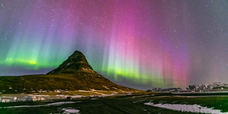 The colorful Northern lights dance behind one of many Iceland's mountains