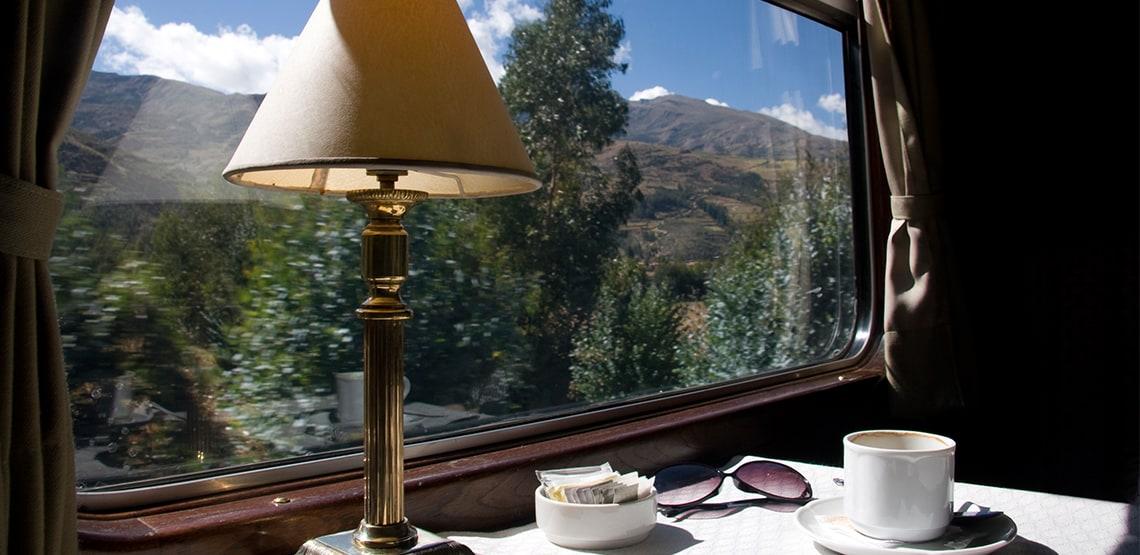 Window on a train with table, lamp, mug, sunglasses