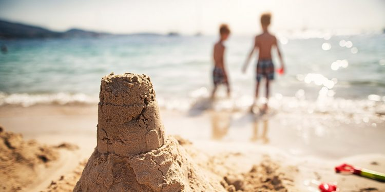 A handmade sand castle is in focus with two young children in the background