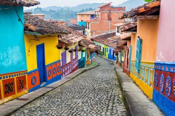 A cobblestone road contains numerous houses are painted with colorful vibrant colors of yellows, blues, pinks, reds, purples, and greens on either side